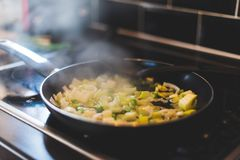 Leeks and other vegetables are being cooked in a frying pan royalty free stock photography