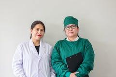 Leende för två asiatiskt medicinska arbetare Stående av den asiatiska doktorn arkivfoto