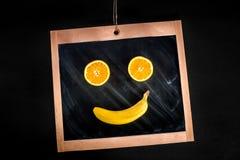 Leendeapelsin och banan på den svart tavlan Fotografering för Bildbyråer