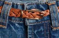 Leer bruine gevlechte die riem in jeansclose-up wordt geplooid stock afbeeldingen