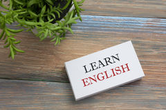 Leer Engelse Teksten die op notitieboekjepagina, rode potlood en koffiekop worden geschreven De bovenkantmening van de bureaulijs Stock Foto