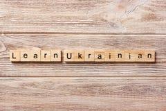 Leer OEKRAÏENS die woord op houtsnede wordt geschreven leer OEKRAÏENSE teksten op lijst, concept royalty-vrije stock foto
