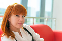 Leer red-haired girl. In the office Royalty Free Stock Photos