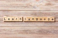 Leer taalwoord op houtsnede wordt geschreven die Leer taaltekst op lijst, concept stock afbeeldingen