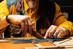 Leerambacht voor portefeuille die met hulpmiddel aan bureau van het leer het craftman ` s werk werken Stock Foto's