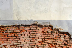 Leere alte Backsteinmauer-Beschaffenheit Die schäbige Fassade des Gebäudes mit schädigendem Gips Stockfotografie