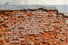 Leere alte Backsteinmauer-Beschaffenheit Die schäbige Fassade des Gebäudes mit schädigendem Gips Stockbilder