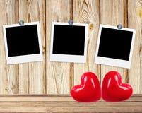 Leere alte Fotos auf Clipn und rote Herzen auf hölzernem Hintergrund Stockfotografie