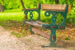 Leere alte hölzerne und Schmiedeeisenbank im Park Lizenzfreie Stockfotografie
