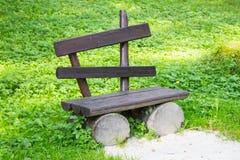 Leere alte Holzbank auf einem grünen Rasen Garten oder Park, draußen Lizenzfreies Stockfoto