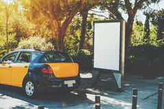 Leere Anschlagtafel nahe gelbem Taxi Lizenzfreies Stockfoto