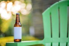 Leere Aufkleber-Bierflasche auf grünem Gartenstuhl Stockbild