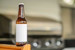 Leere Aufkleber-Bierflasche auf Tabelle nahe Grill Lizenzfreies Stockbild
