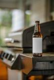 Leere Aufkleber-Bierflasche, die auf Rand des Grills sitzt Lizenzfreie Stockfotos