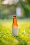 Leere Aufkleber-Bierflasche im Gras Stockbilder