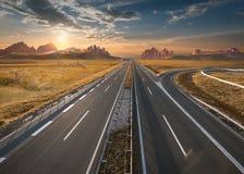 Leere Autobahn durch Weite bei idyllischem Sonnenuntergang Stockfoto