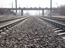 Leere Bahnlinien, Schienen, Lagerschwellen, Schutt und Transportbrücke fern, Abschluss oben, Weitwinkel-, getontes Braun, selekti stockbilder