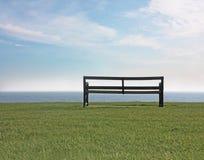 Leere Bank an der Küste Stockfoto