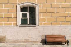 Leere Bank gegen die Wand mit einem Fenster lizenzfreie stockbilder