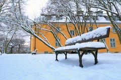 Leere Bank im Park am schneebedeckten Winter Stockbilder