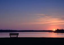 Leere Bank am Sonnenuntergang Stockbilder