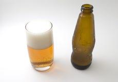 Leere Bierflasche und Glas Bier Stockfoto