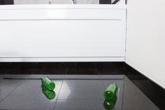 Leere Bierflaschen auf schwarzem Granitboden Lizenzfreie Stockfotos