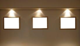 Leere Bilderrahmen auf der Wand mit Beleuchtung Lizenzfreie Stockbilder