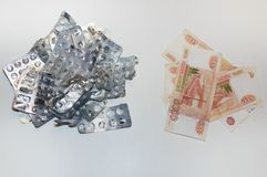 Leere Blasen von den Pillen und viele Rubelrechnungen auf einem weißen Hintergrund Das Konzept von hohen Kosten Drogen lizenzfreie stockfotos