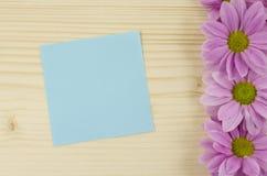 Leere blaue Karte und rosa Blumen auf hölzernem Hintergrund Lizenzfreie Stockfotos