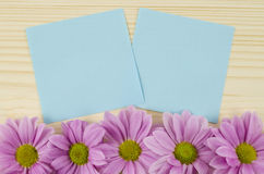 Leere blaue Karten und rosa Blumen auf hölzernem Hintergrund Lizenzfreies Stockfoto