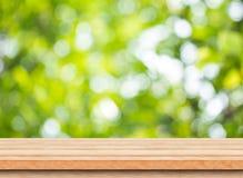 Leere braune hölzerne Tischplatte mit Unschärfegrünbaum bokeh Hintergrund lizenzfreie stockfotografie