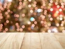 Leere braune Holztischspitze der Nahaufnahme mit defocused kleinem buntem Weihnachtslichter bokeh Hintergrund Lizenzfreies Stockfoto
