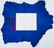 Leere Broschüre mit Bleistift auf einem blauen Ziegenfell Lizenzfreies Stockfoto