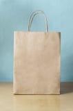 Leere Brown-Einkaufstasche auf Tabelle mit blauem Hintergrund Stockbild