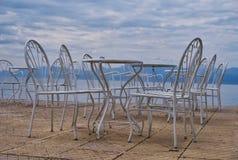 Leere Café-Tabellen neben Meer, Griechenland Lizenzfreies Stockbild
