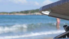 Leere Chaise Longue Under Sun Umbrella auf der Ozean-Küste stock video