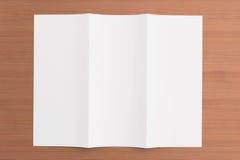 Leere dreifachgefaltete Broschüre auf hölzernem Hintergrund Lizenzfreies Stockbild