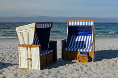 Leere ein Sonnenbad nehmende Körbe auf leerem Strand Stockbild