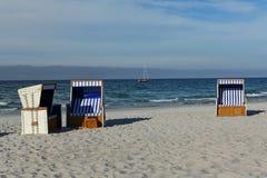 Leere ein Sonnenbad nehmende Körbe auf leerem Strand Lizenzfreies Stockbild