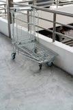 Leere Einkaufsfracht auf dem Zementboden verlassen durch Metallscheune b lizenzfreie stockfotos