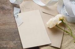 Leere Einladungskarte mit braunem Umschlag und rosafarbene Blumen auf wo Stockfoto