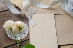 Leere Einladungskarte mit braunem Umschlag und rosafarbene Blumen auf wo Lizenzfreie Stockbilder