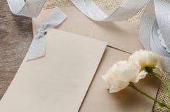 Leere Einladungskarte mit braunem Umschlag und rosafarbene Blumen auf wo Stockbild