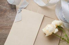 Leere Einladungskarte mit braunem Umschlag und rosafarbene Blumen auf wo Stockbilder