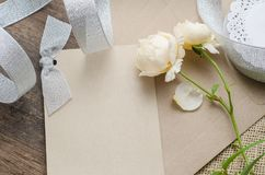 Leere Einladungskarte mit braunem Umschlag und rosafarbene Blumen auf wo Stockfotos