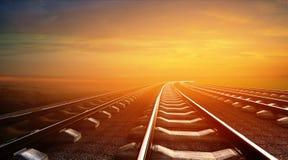 Leere Eisenbahnen auf Sonnenunterganghimmelhintergrund Stockfoto