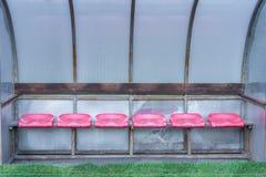 Leere Ersatzbank nahe bei einem Fußballplatz stockbild