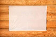 Leere Flagge des Stoffes die hölzerne Blockhauswand hängend hergestellt von cylindered Klotz Lizenzfreies Stockfoto