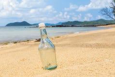 Leere Flaschen auf dem Sandstrand lizenzfreie stockbilder
